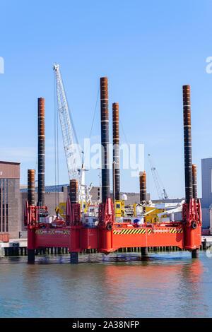 La construction d'une barge flottante avec un godet grab et crane, a quatre de ses huit spud-jambes vers le bas, à faire reposer sur le fond de la mer alors qu'il drague. Port Banque D'Images
