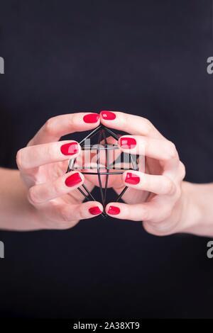 Belle femme hands holding black metal frame diamond. Manucure avec vernis à ongles rouge. Fond noir