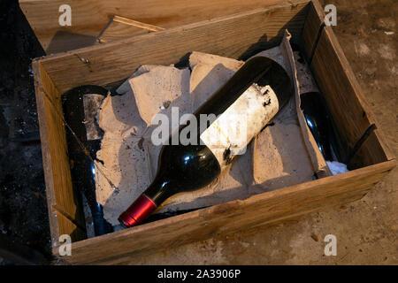 Vieille bouteille de vin poussiéreux dans une boîte dans la cave, Banque D'Images