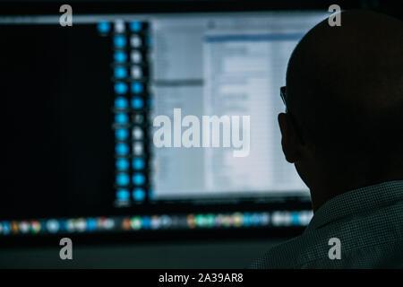 Développeur, situé derrière le bureau, l'analyse de schéma à l'écran Banque D'Images