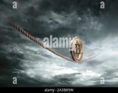 Coin Bitcoin en équilibre sur la corde sur ciel dramatique with copy space Banque D'Images