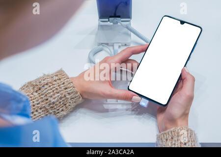 Maquette: woman looking at Smartphone avec écran blanc au magasin, boutique