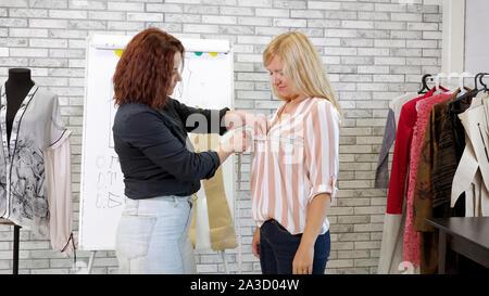 Couturière travaille dans l'atelier. Couturière prend des mesures avec du ruban de femme dans l'adaptation à la clientèle de l'atelier. L'adaptation individuelle à l'ordre. Entreprise de couture. Banque D'Images