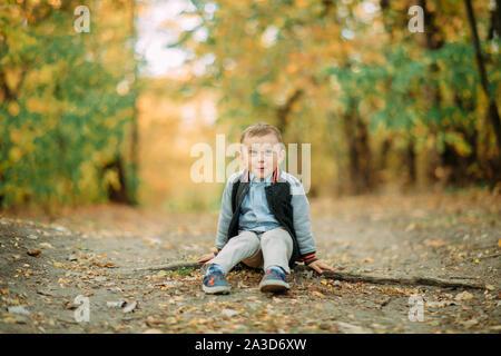 Un enfant garçon est assis sur un chemin en marchant dans la forêt d'automne.