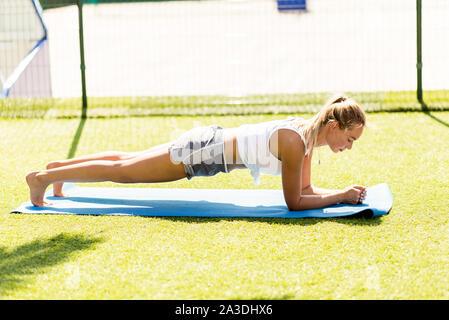 Perfect plank. Long side view of young Beautiful woman in sportswear faisant plank en étant debout sur la pelouse de l'avidité Banque D'Images