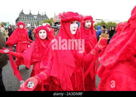 Westminster, London, UK - Lundi 7 octobre 2019 - La Rébellion de la Brigade Rouge Extinction XR danseurs défilé à travers le pont de Westminster dans le vent et la pluie le jour 1 de la XR de protestation. Photo Steven Mai / Alamy Live News