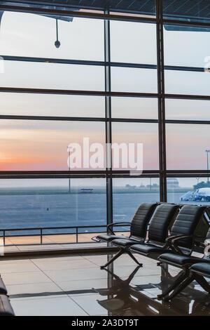 Voir l'aéroport de interoir chaises banc vide, dans le hall de départ pendant le lever du soleil. La construction d'avions et d'arrière-plan. Voyages et transport concept Banque D'Images