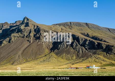 Ferme celandique près de Grundarhverti juste au nord-ouest de Reykjavic sous les montagnes de roches volcaniques, un paysage islandais typique. Banque D'Images