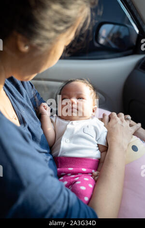 Portrait of infant baby portant sur les genoux de mère tandis que dans la voiture Banque D'Images