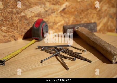 Des clous et marteau ruban de mesure sur table en bois Banque D'Images