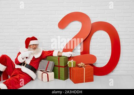 Senior male caractère noël en costume rouge assis sur sol blanc avec papier cadeaux et nombres en couleur de 20. Santa Claus with presents in white studio Banque D'Images
