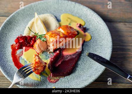 Vue de dessus du délicieux poisson grillé servi avec des fruits garnir sur la plaque. Morceau de viande avec la fourchette et le couteau. Délicieux repas accompagné de sauce et de citron. Concept de l'alimentation et la vitamine. Banque D'Images