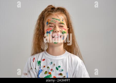 Petite fille en t-shirt blanc, avec visage peint fait des grimaces tout en se posant isolé sur blanc. Art Studio. Close-up. Banque D'Images