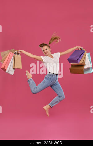 Femme blonde avec des queues de cheval, habillé en blanc T-shirt et jeans posant contre un fond rose avec des paquets. Pleine longueur. Les émotions, le shopping. Banque D'Images