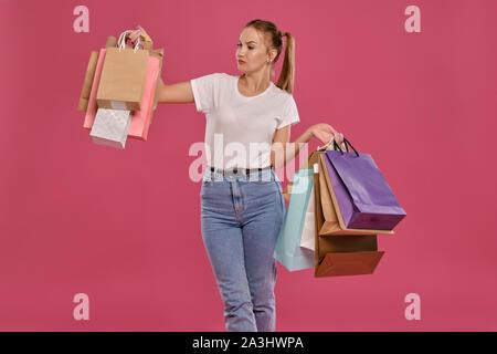Femme blonde avec des queues de cheval, habillé en blanc T-shirt et jeans posant contre un fond rose avec des paquets. Close-up. Des émotions sincères, shopping. Banque D'Images