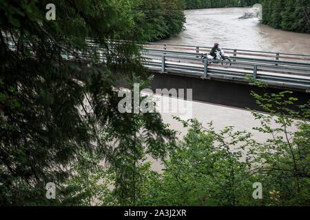 Une femme rides sa motocyclette sur un pont, sur une journée d'été.