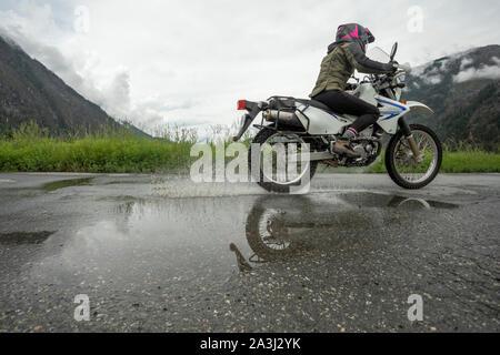 Une femme sur une moto en son ciel nuageux jour d'été.