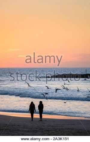 Israël, Tel Aviv, Tel Aviv. Les gens sur la plage de Frishman pendant le coucher du soleil. Banque D'Images