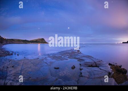 Jupiter (centre) et Saturne (centre gauche) dans le ciel de nuit plus Kimmerridge Bay, Côte Jurassique, Dorset, England, UK Banque D'Images