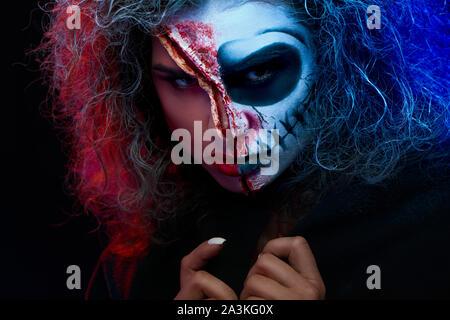 Portrait de jeune femme charmante avec peur maquillage halloween portant cape noire looking at camera avec de mystérieux de l'expression du visage. Le Jour des Morts. L'Halloween. Banque D'Images