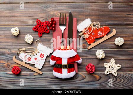 Vue du haut de fourchette et couteau sur serviette sur fond de bois. Les différentes décorations de Noël et les jouets. Close up de nouvelle année le dîner concept. Banque D'Images