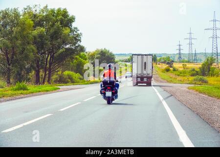 Samara, Russie - le 17 août 2019: Biker dans un casque noir se déplace sur une route asphaltée. Soft focus Banque D'Images