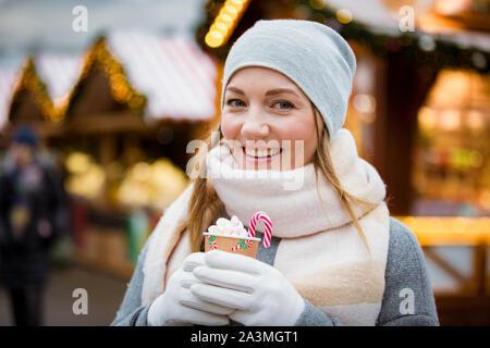 Jeune femme au marché de Noël de boire tasse de chocolat chaud avec de la guimauve en portant chapeau chaud et écharpe. Boutiques décorées et lumineuses