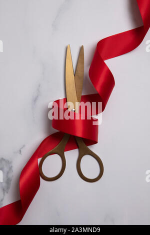 Grand Fond d'ouverture. Ciseaux d'or avec ruban rouge sur un fond de marbre Banque D'Images