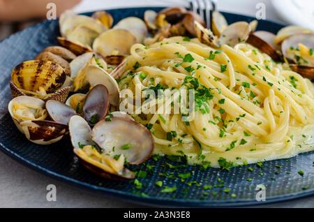 Une assiette de pâtes avec les palourdes et la sauce. Des plats italiens traditionnels. Spaghetti alle vongole ou pâtes Posillipo. Banque D'Images