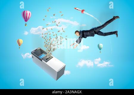 Businessman reaching à ATM machine avec des dollars de prendre l'avion, des montgolfières et argent rouge fusée spatiale dans l'air sur fond bleu Banque D'Images