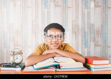 Young attractive asian male student smiling while looking at camera sitting contre table avec des livres. Concept de l'éducation, professionnels et étudiants expressi Banque D'Images
