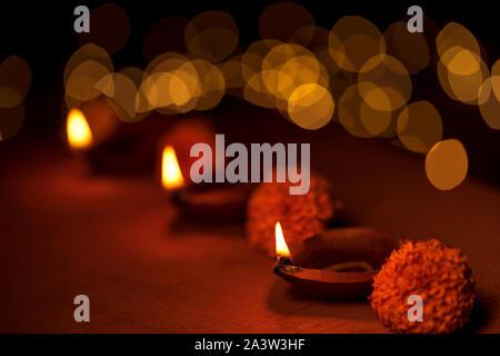 Décoration traditionnelle avec Diwali diya lampes à huile, fleurs de souci et golden bokeh pendant Diwali fête la nuit. Banque D'Images