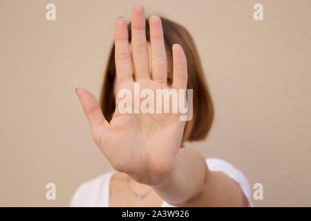 Jeune femme sérieuse montrant main stop sign, sur fond isolé
