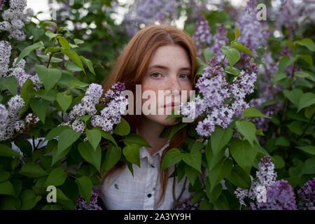 Teenage girl parmi fleurs violettes