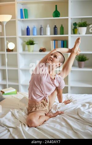 Smilng femme charmante et remise en forme en faisant des exercices à domicile pyjama sur lit. Concept de vie sain