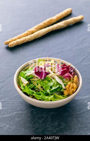 Saladier automne sain le déjeuner avec des noix, de la laitue, des épinards aux graines de sésame Banque D'Images