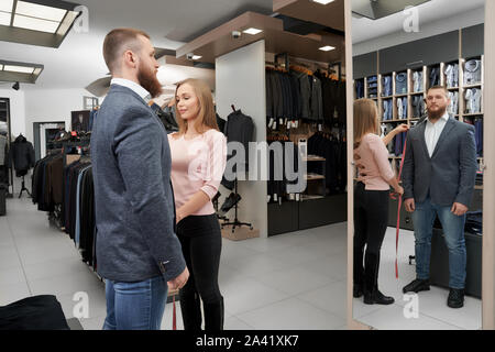 Vue latérale d'hommes barbus à la clientèle à miroir et de choisir de nouveaux smart costume. Jeune homme à la mode tout en essayant sur Veste femme mesure de la longueur de la gaine en boutique. Concept de vêtements. Banque D'Images