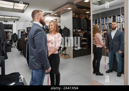 Femme attrayante de mesure sur mesure Longueur de manche de veste dans une boutique. Jeune homme barbu essayer client sur les vêtements, à la recherche de miroir et choisissant smart décontracté costume dans l'atelier. Concept de montage. Banque D'Images