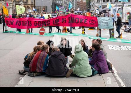Jeunes manifestants assis en train de discuter en groupe à une rébellion d'Extinction road block sur la rue Victoria, Westminster, London
