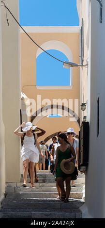 Fira, Grèce - 12 juillet 2019: Des touristes se promènent le long d'un des peu nombreux de Fira off Agiou Ioannou, côté rue Banque D'Images