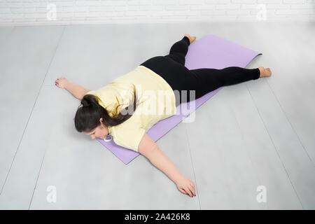 Femme avec corps en courbes, en jaune et noir à capuche legging est allongé sur le tapis violet dans la posture de l'étoile après une formation à l'intérieur. Jeune fille brune qui reste après l'entraînement intensif. Banque D'Images