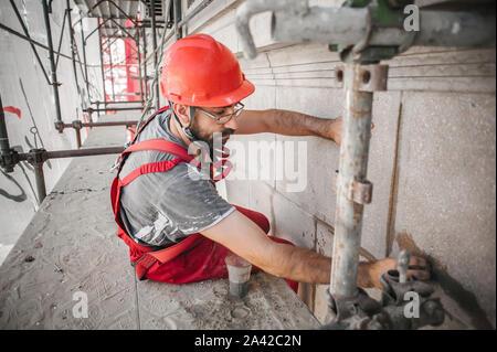 Travailleur de la construction mason sur l'échafaudage de mélanger du ciment et du sable à l'aide d'une spatule sur le site de construction
