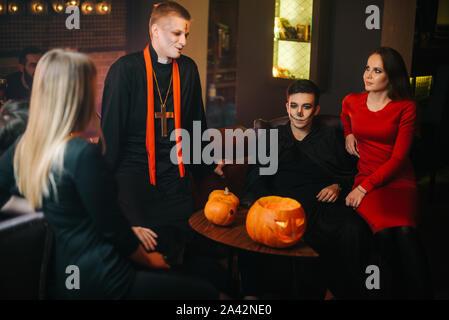 Portrait de groupe de jeunes gens dans des costumes de Halloween sitting in cafe Banque D'Images