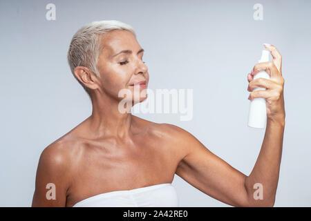 Gardant les yeux clos blonde détendue pendant la pulvérisation de l'eau thermique sur son visage