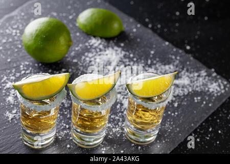 Trois verres de tequila mexicaine d'or et de chaux avec du sel sur fond sombre Banque D'Images