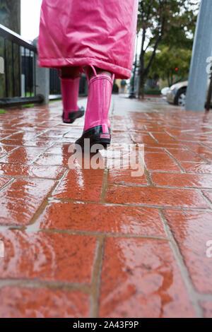 Une marche sous la pluie avec des bottes rose et un imperméable. Banque D'Images