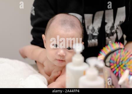 Mère donner une baignoire son bébé garçon dans une salle de bains privative. Enfant est âgé de 4 mois. Banque D'Images