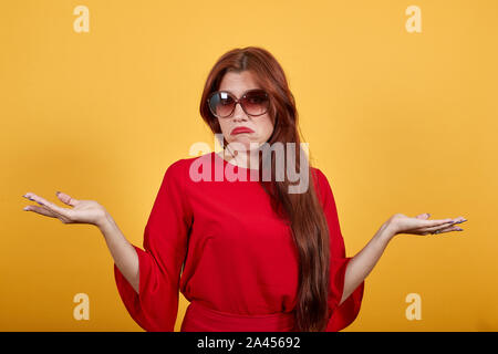 Jeune femme au mur de lumière ayant des doutes en levant les mains. Banque D'Images