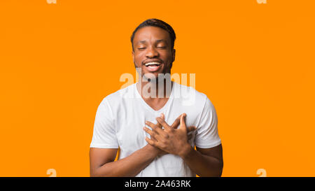 Guy Afro tenant les mains sur la poitrine l'article dans Studio, Panorama