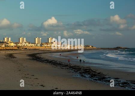 Personnes marchant sur une plage de Jersey dans les îles de la Manche, pendant le coucher du soleil, avec un horizon de hôtels et autres bâtiments en arrière-plan. Banque D'Images